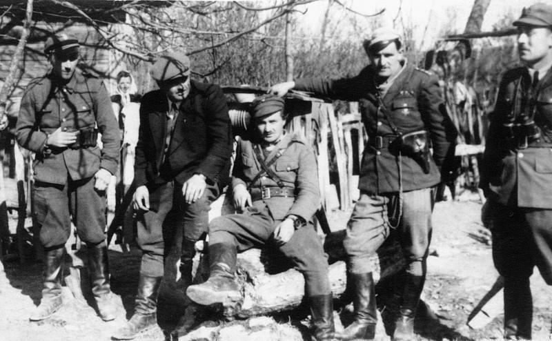 """Oddział Stanisława Łukasika """"Rysia"""". Prawdopodobnie w mundurze siedzący na studni to """"Mundek"""". Na prawo od niego """"Ryś"""", na lewo Władysław Misztal """"Bór"""""""